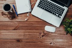 Tavola di legno della scrivania con il computer portatile, la tazza di caff? ed i rifornimenti fotografia stock
