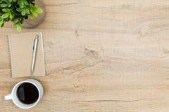 Tavola di legno dello scrittorio dei pantaloni a vita bassa con il taccuino e penna, caffè ed albero Immagini Stock