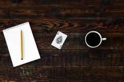 Tavola di legno di Brown con la carta della tazza di caffè, del taccuino, della matita e dell'asso Vista superiore Immagine Stock Libera da Diritti
