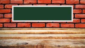Tavola di legno e muro di mattoni rosso sui precedenti fotografia stock