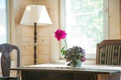 Tavola di legno invecchiata con il vaso ed i fiori di fiore fotografia stock