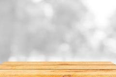 Tavola di legno marrone vuota e fondo interno della sfuocatura con l'immagine del bokeh, per il montaggio dell'esposizione del pr Immagine Stock