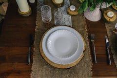 Tavola di legno messa con le candele, il piatto bianco ed il tovagliolo grigio immagini stock