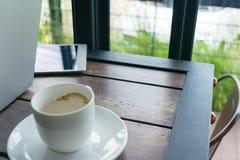 Tavola di legno nel ristorante con caffè ed il computer portatile Fotografia Stock