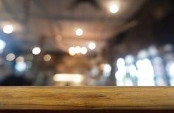 Tavola di legno scura vuota davanti a fondo vago astratto dell'interno del ristorante, del caffè e della caffetteria può essere u fotografie stock