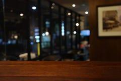 Tavola di legno su sfuocatura del caffè, la caffetteria, la barra, fondo - possono usato per esposizione o il montaggio i vostri  immagine stock