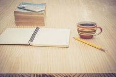 Tavola di legno superiore nel posto di lavoro con il libro e la matita del blocco note della tazza di caffè per il concetto di la Fotografia Stock