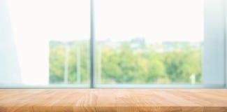 Tavola di legno vuota con il fondo di vista della finestra della sfuocatura fotografie stock libere da diritti