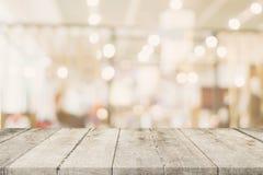Tavola di legno vuota con la gente astratta vaga sul caffè sul resta Fotografia Stock