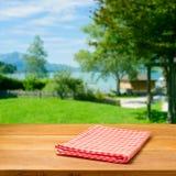 Tavola di legno vuota con la tovaglia controllata sopra bello paesaggio. immagine stock