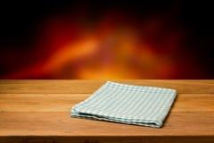 Tavola di legno vuota con la tovaglia controllata sopra il fondo del fuoco della sfuocatura. Fotografie Stock Libere da Diritti