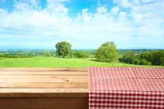 Tavola di legno vuota con la tovaglia sopra il fondo di estate immagine stock libera da diritti