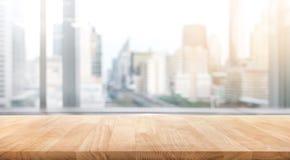 Tavola di legno vuota con la vista dell'ufficio della stanza della sfuocatura e della città della finestra immagine stock