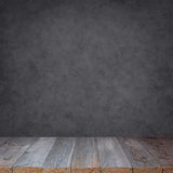 Tavola di legno vuota contro una parete grigia immagine stock