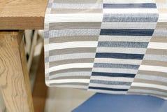 Tavola di legno vuota coperta di panno a strisce di tela della cucina e di precedenti vaghi, bokeh fotografia stock