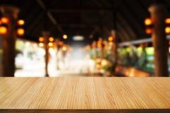 tavola di legno vuota davanti al fondo dell'estratto del montaggio della sfuocatura immagine stock