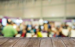 Tavola di legno vuota davanti alla gente vaga in sala Fotografie Stock