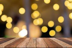 Tavola di legno vuota nel fondo giallo vago parte anteriore, per la presentazione fotografie stock libere da diritti