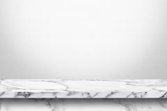 Tavola di marmo vuota con il fondo grigio bianco della parete di pendenza immagine stock