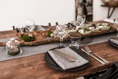 Tavola di nozze decorata dai piatti, coltelli e forcelle, albero e muschio Interiore scandinavo Fotografia Stock