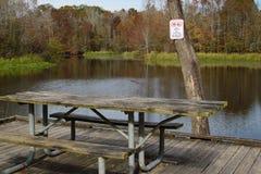 Tavola di picnic con il segnale di pericolo dell'alligatore Immagini Stock Libere da Diritti