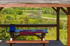 Tavola di picnic con una vista di un fiume Fotografia Stock