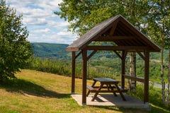 Tavola di picnic riparata con la vista di un fiume Fotografie Stock