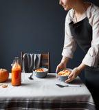 Tavola di prima colazione di servire della donna su grigio fotografia stock