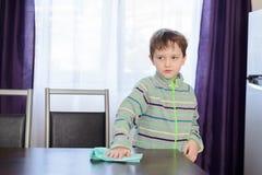 Tavola di pulizia del ragazzo in cucina immagini stock libere da diritti