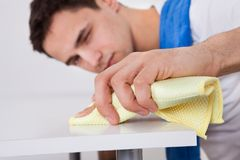 Tavola di pulizia dell'uomo con il tovagliolo a casa Immagine Stock