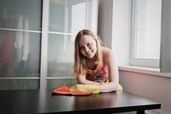 Tavola di pulizia della ragazza con la lucidatura della mobilia a casa fotografia stock libera da diritti
