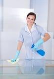 Tavola di vetro di pulizia della domestica felice immagini stock