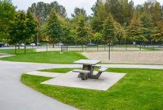 Tavola e banchi di picnic su prato inglese verde in un parco immagine stock libera da diritti