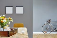 Tavola e bici d'annata interne moderne di sguardo in due stanze fotografie stock