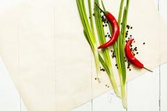 Tavola e posto di legno bianchi per un piatto su un piatto Peperone e cipolle verdi immagini stock libere da diritti