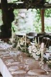 Tavola elegante decorata di nozze per la cena con i mazzi, i candelieri ed i vetri bianchi floreali di una tovaglia di bianco e immagine stock