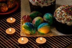 Tavola festiva per Pasqua Ci sono due dolci di Pasqua sulla tavola, parecchie uova di Pasqua stanno trovando, candele stanno bruc fotografia stock