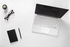 Tavola minimalistic alla moda dello scrittorio con il computer portatile, il cactus, gli occhiali, il taccuino e la penna Area di Immagine Stock Libera da Diritti