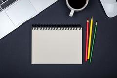 Tavola moderna della scrivania con il computer portatile e la pagina in bianco del taccuino Immagini Stock