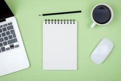 Tavola moderna della scrivania con il computer portatile e la pagina in bianco del taccuino Immagine Stock