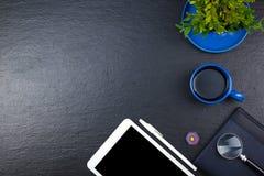 Tavola nera della scrivania con il computer, penna e una tazza di caffè, lotto delle cose Vista superiore con lo spazio della cop Fotografia Stock Libera da Diritti