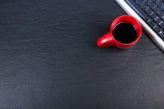 Tavola nera della scrivania con il computer, penna e una tazza di caffè, lotto delle cose Vista superiore con lo spazio della cop Fotografia Stock