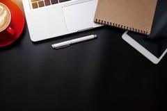 Tavola nera della scrivania con molta tazza di cose compressa, del computer portatile, dello smartphone, del blocco note e di caf fotografie stock libere da diritti