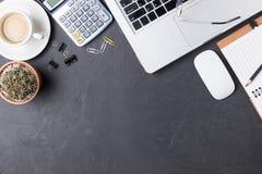 Tavola nera dello scrittorio dell'ufficio con il calcolatore, nota di carta, rifornimenti fotografia stock