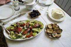 Tavola posta con i piatti di insalata delle verdure e del formaggio della pecora Fotografia Stock