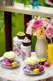 Tavola posta con il mazzo delle rose rosa, dei bigné e di due tazze con le rose Fotografia Stock Libera da Diritti