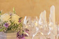 Tavola premio di galà della cena con i tovaglioli ed i vetri dei fiori in ro Fotografia Stock