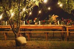 Tavola pronta per una cena all'aperto rustica alla notte con il winegla fotografia stock