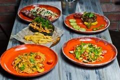 Tavola servita con i vari piatti del ristorante Hot dog, costole di carne di maiale del barbecue, bistecca, pasta di Carbonara ed fotografia stock
