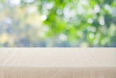 Tavola vuota con la tovaglia di tela marrone sopra la natura vaga del parco fotografia stock libera da diritti